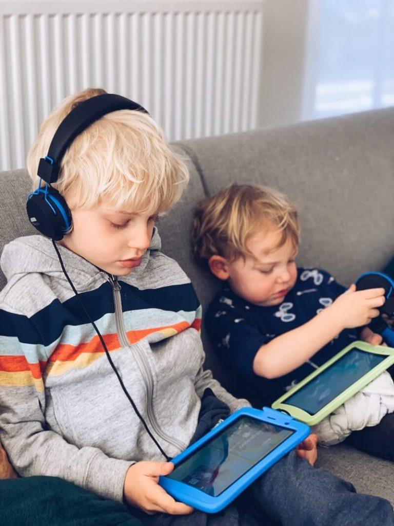Kinderen luisteren muziek op de bank